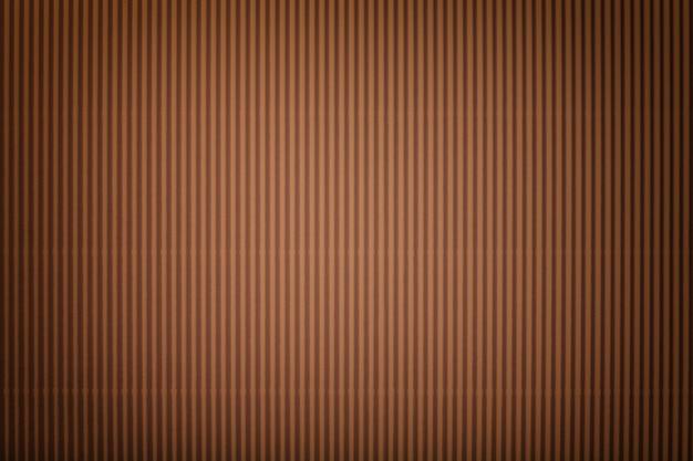 Texture di carta ondulata marrone scuro con vignetta, macro. sfondo di cartone bronzo a strisce, primo piano.