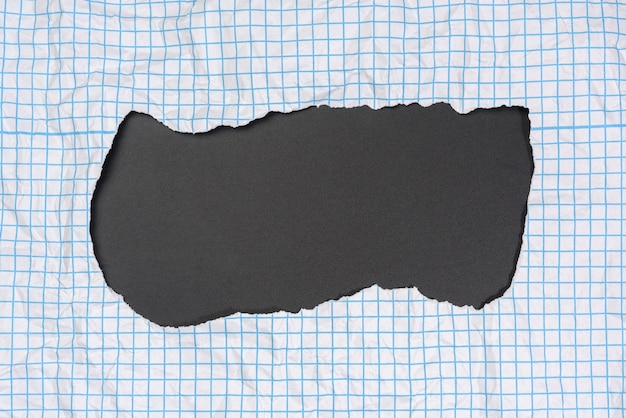 Texture di carta bianca stropicciata in una gabbia, linee blu, bordi strappati su sfondo nero