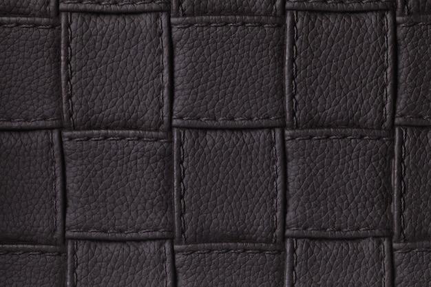 Texture di sfondo scuro in pelle nera con design quadrato e punto, macro.