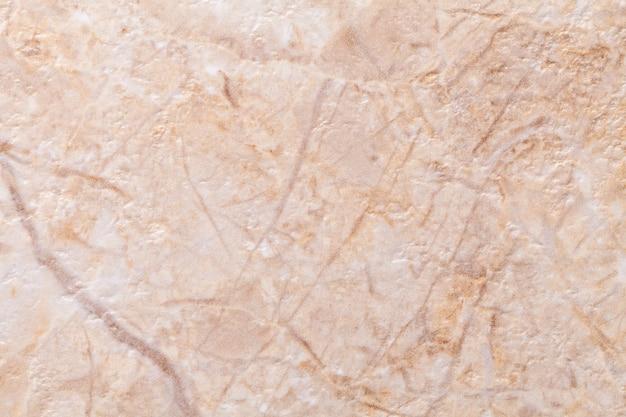 Texture di intonaco beige decorativo che imita il vecchio muro di pietra scrostata. crema obsoleta e sfondo marrone incrinato, primo piano.