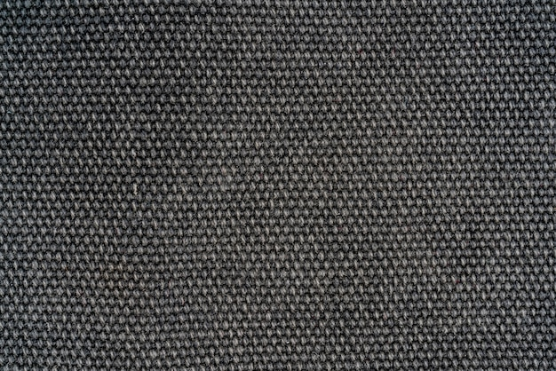 La trama di un tessuto di lana grigio denso. priorità bassa della tessile del primo piano.