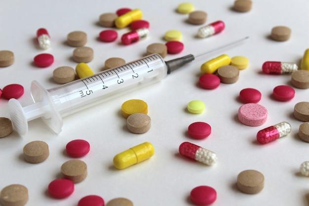 Texture di diversi farmaci su un tavolo grigio con una siringa