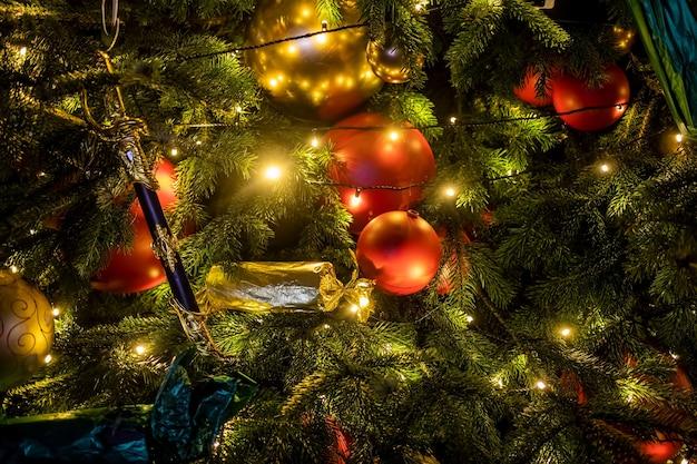 Trama di abete ramo con giocattoli di luci e decorazioni. un frammento di capodanno e albero di natale. primo piano, messa a fuoco morbida, sfocatura dello sfondo