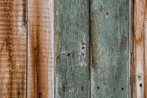 La trama è un vecchio legno, danneggiato con vernice screpolata, con buchi.