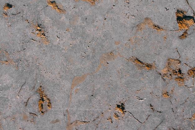 La trama di una pietra grigia naturale con impregnazioni dorate. copia spazio sfondo di pietra