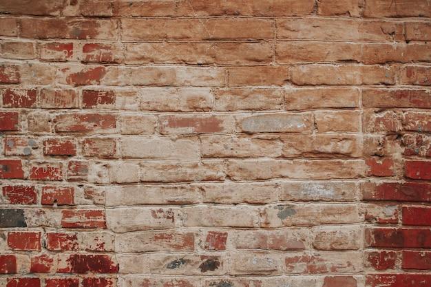 La trama di un vecchio muro di mattoni con difetti naturali, graffi, crepe, fessure, scheggiature, rugosità della polvere...