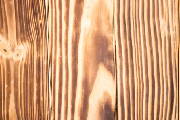 La trama del vecchio legno bruciato con graffi e irregolarità