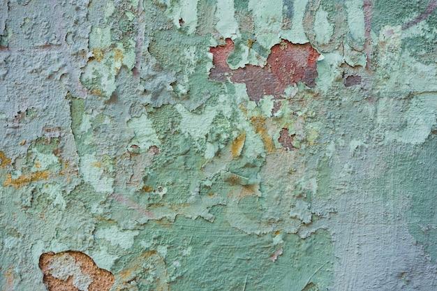 Texture di un vecchio muro con vernice scrostata verdastra