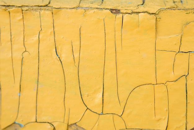 Struttura di vecchio legno con vernice gialla con le crepe