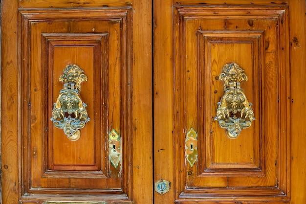 Struttura di una vecchia porta di legno di legno con maniglie di metallo insolite sull'isola di malta
