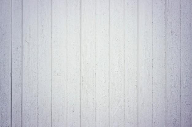 La trama del foglio profilato è bianca, una recinzione metallica. per il tetto. recinzione in alluminio. piastra a muro in acciaio zincato. pannelli profilati in lamiera grecata. linee verticali. texture di metallo di ferro.