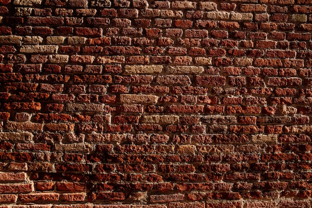 Texture di un muro di mattoni rossi illuminato dal sole pomeridiano con sfondo spazio copia.