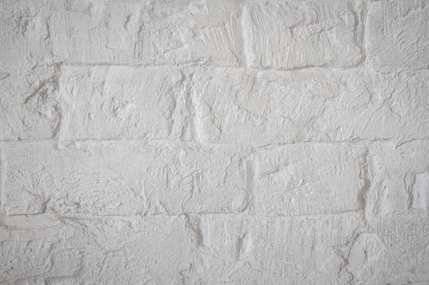 Struttura del primo piano grezzo della muratura bianca. intonaco di fondo sopra i mattoni.