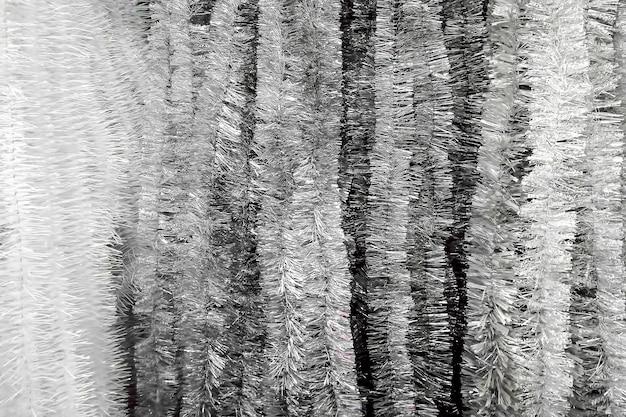 Texture argento lucido capodanno natale tinsel pioggia verticale. primo piano, messa a fuoco morbida.