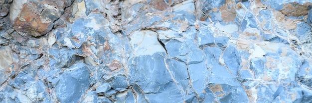 La trama della superficie delle rocce di pietra naturale blu grigio come sfondo. banner