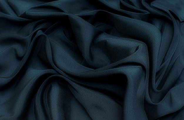La trama del tessuto sintetico è verde scuro. sfondo, modello.