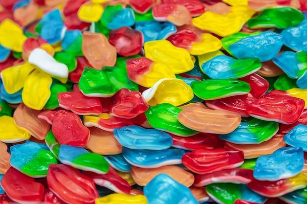 Texture di caramelle di gelatina gialle, rosse e verdi e blu. dolci su un mucchio da vicino. vetrina del negozio di dolci.