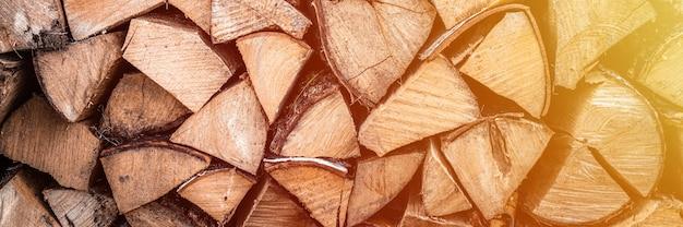 Fondo strutturato della legna da ardere di legno tagliato per accendere e riscaldare la casa una catasta di legna con legna da ardere impilata. la trama dell'albero di betulla. bandiera. bagliore