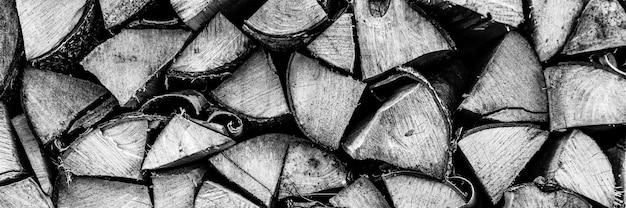 Fondo strutturato della legna da ardere di legno tagliato per accendere e riscaldare la casa una catasta di legna con legna da ardere impilata. la trama dell'albero di betulla. tonica in colore bianco nero o grigio. striscione