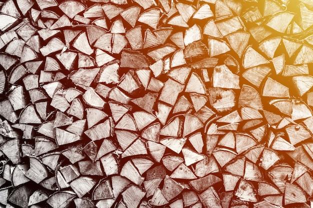 Fondo strutturato della legna da ardere di legno tagliato per accendere e riscaldare la casa una catasta di legna con legna da ardere impilata. la trama dell'albero di betulla. tonica in colore bianco nero o grigio. bagliore