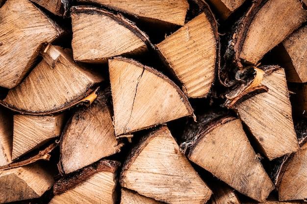 Fondo strutturato della legna da ardere di legno tagliato per accendere e riscaldare la casa una catasta di legna con legna da ardere impilata. la trama dell'albero di betulla
