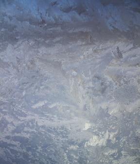 Motivi di brina testurizzati sul vetro. cristalli di ghiaccio sulla finestra in una fredda giornata gelida d'inverno.