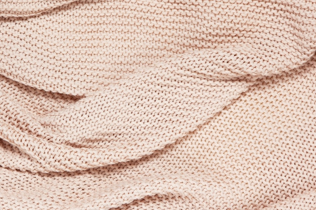 Superficie testurizzata di plaid a onde di cotone lavorato a maglia, vista dall'alto, primo piano. sfondo di lana pastello rosa polveroso morbido.