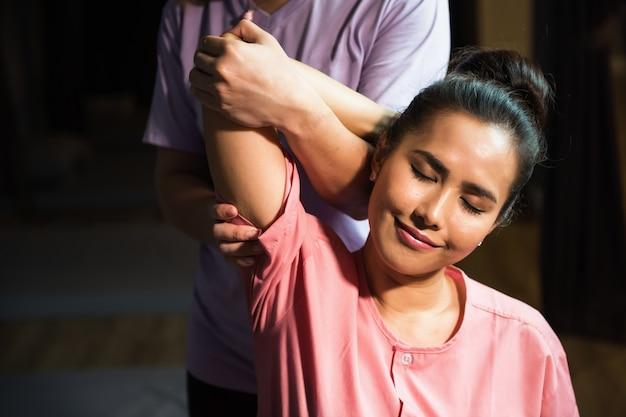 Terapia di massaggio riflessologico tailandese del braccio e del gomito alla giovane bella donna asiatica sul divano nel salone della stazione termale. assistenza sanitaria e relax per curare il concetto di dolore. settore sanitario alternativo.