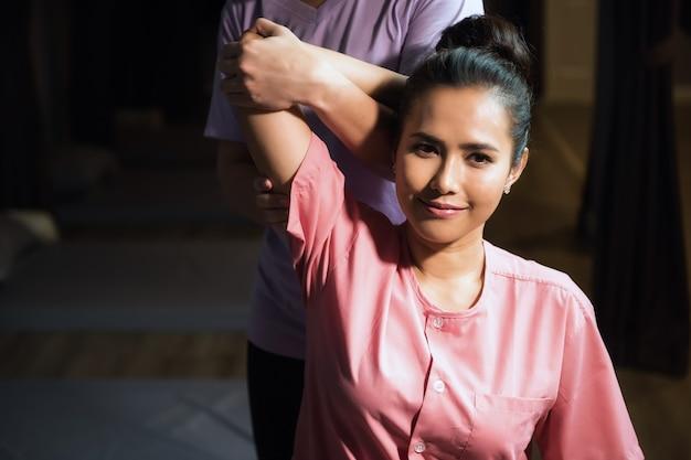 Massaggio di riflessologia tailandese del braccio e del gomito a una giovane bella donna asiatica in spa