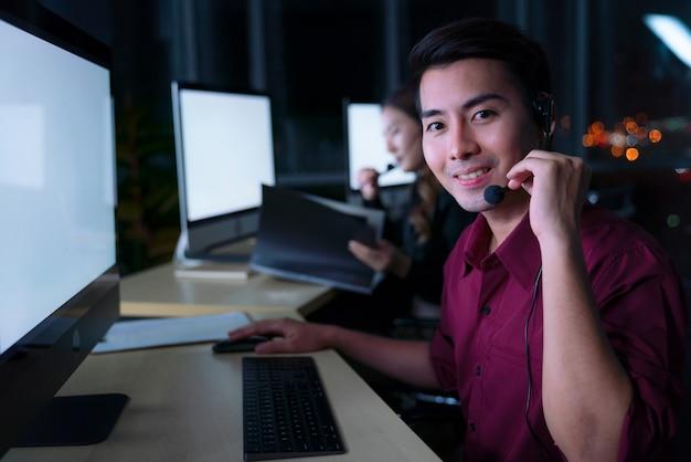 Operatori di assistenza clienti uomo asiatico tailandese che lavorano il turno di notte nel call center