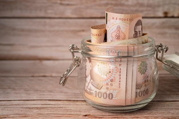 Banconote in baht thailandese in vaso di erba su sfondo di legno.