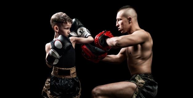 Allenatore di boxe thailandese che pratica pugni con il suo studente. concetto di kickboxing, mma. tecnica mista