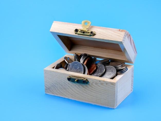 Moneta tailandese nella cassa di legno su fondo blu