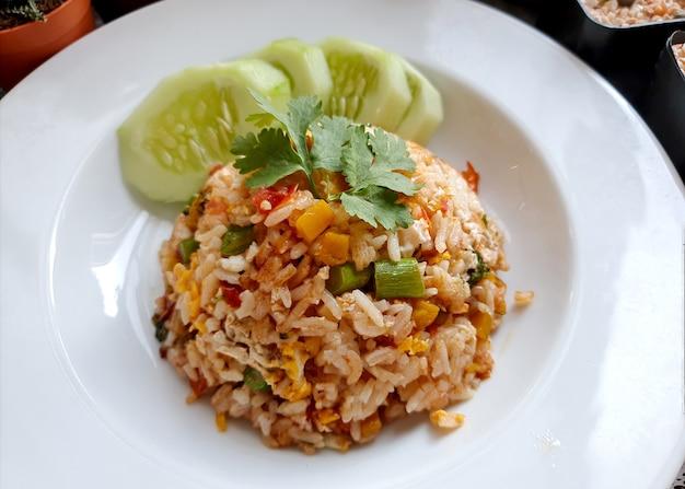 Riso fritto tailandese dell'uovo con il cetriolo affettato fresco su un piatto bianco