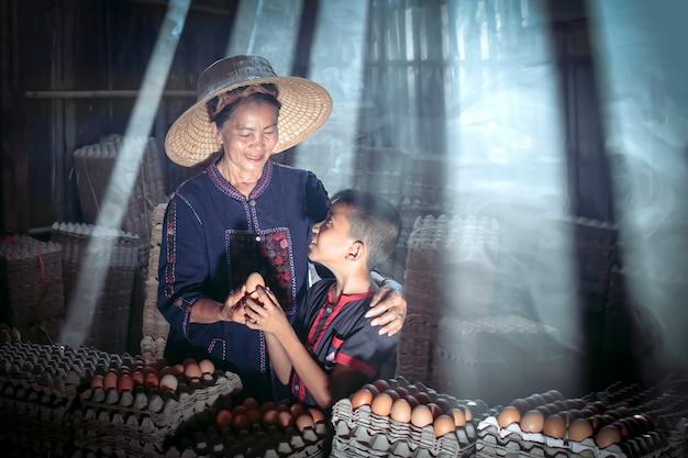 Madre e figlio dell'agricoltore thailandese sono felicissimi che l'uovo, che è un buon prodotto