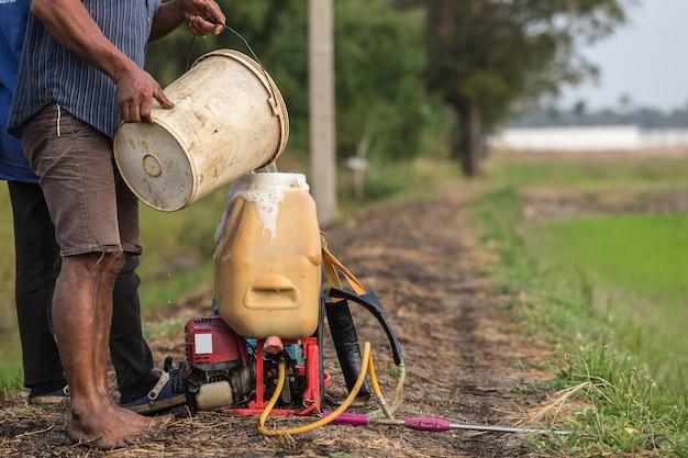 L'agricoltore tailandese prepara il prodotto chimico al carro armato dello spruzzatore prima di spruzzare al giovane giacimento verde del riso