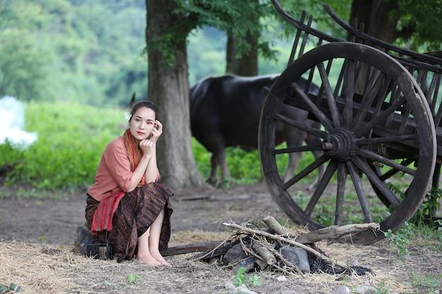 Coltivatore tailandese che indossa la tradizione tailandese locale che si siede nella sua fattoria