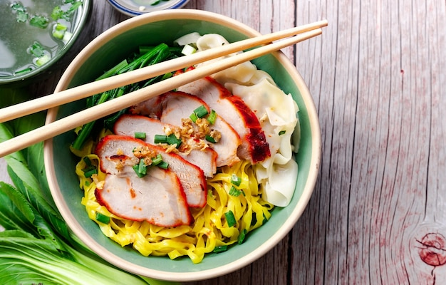 Cibo tailandese - egg noodle (giallo) con arrosto di maiale rosso nella ciotola verde e bacchette sopra quella posta sul tavolo di legno in vista dall'alto
