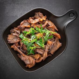 Cibo tailandese, manzo essiccato al sole fritto con foglie di basilico croccanti in padella nera sullo sfondo scuro della trama