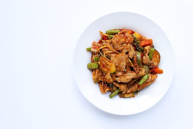 Cibo tailandese, maiale saltato in padella caldo e piccante con erbe