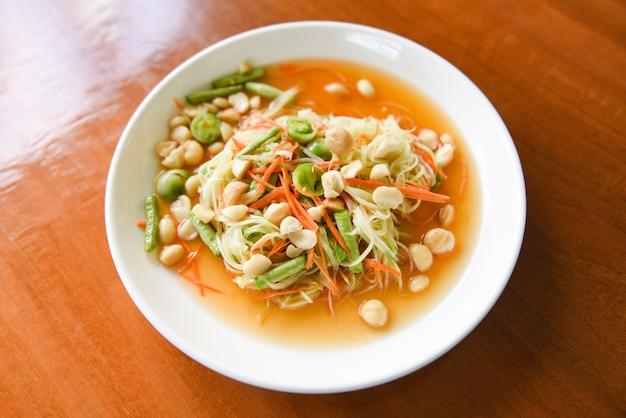 Insalata tailandese della papaya dell'alimento con le noci di macadamia sulla parte superiore sul piatto bianco