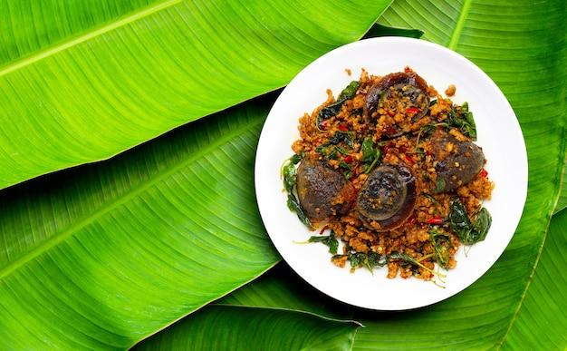 Cibo thailandese. tritato di maiale saltato in padella, uovo conservato con foglie di basilico su foglie di banana.