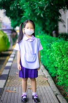 Studentessa tailandese che indossa una maschera di protezione prima di andare a scuola