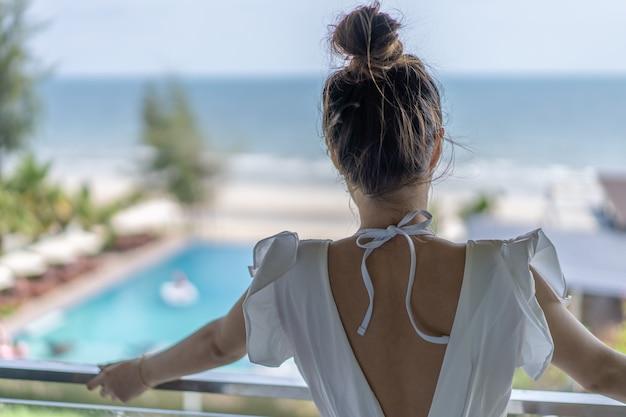 Abito da gril tailandese il codice di abbigliamento da ling whirt è in piedi di fronte alla terrazza della camera da letto con piscina e vista panoramica sul mare di fronte a lei.