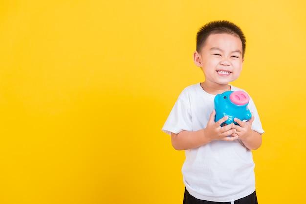 Sorriso del ragazzo del bambino allegro sveglio del ritratto felice tailandese piccolo che tiene banca piggy