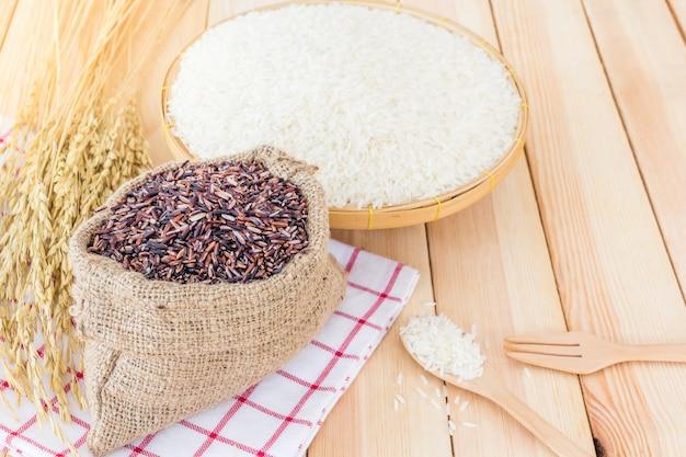 Riso bianco del gelsomino e riso riceberry tailandesi in canestro e borsa di bambù su fondo di legno