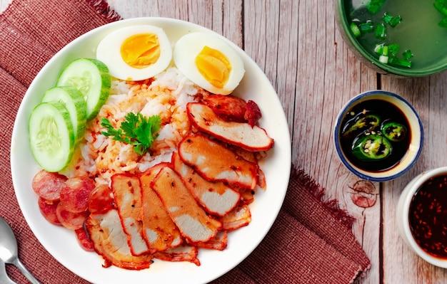 Cibo locale tailandese - arrosto di maiale rosso con riso servito con salsiccia, uova sode e zuppa in vista dall'alto