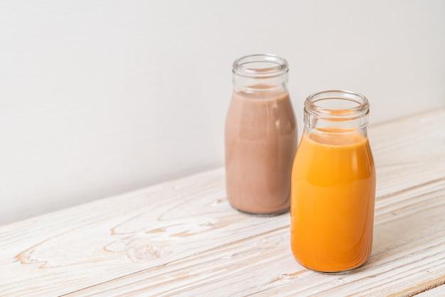 Tè al latte tailandese e latte al cioccolato in bottiglia su fondo di legno