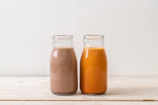 Tè al latte tailandese e latte al cioccolato in bottiglia sulla superficie del legno