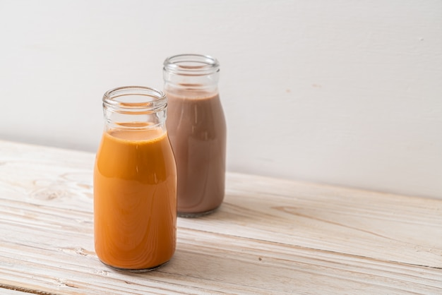 Tè al latte tailandese e latte al cioccolato in bottiglia su legno